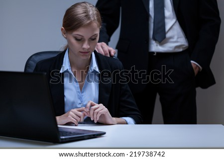 Young attractive employee and problem with her boss - stock photo