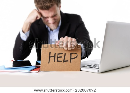 young attractive European businessman working in stress at office desk computer laptop holding help cardboard sign worried and frustrated isolated on white background - stock photo