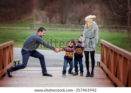 Young attractive family with two kids, young adults having fun outdoors, kissing and hugging - stock photo