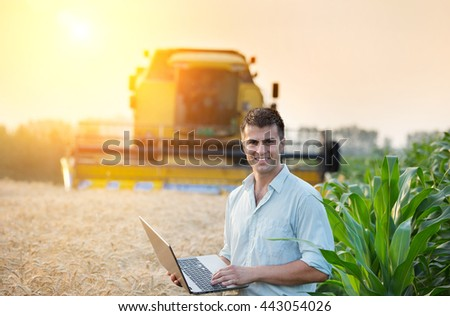 Young attractive farmer holding laptop and standing in corn field while combine harvesting wheat in background - stock photo