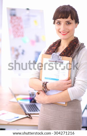 Young attractive fashion designer standing by desk in office, holding folders - stock photo