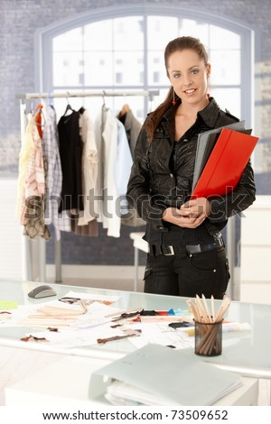 Young attractive fashion designer standing by desk in office, holding folders, smiling. - stock photo