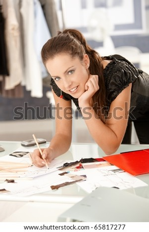 Young, attractive fashion designer working in office, drawing, leaning on desk, smiling.? - stock photo