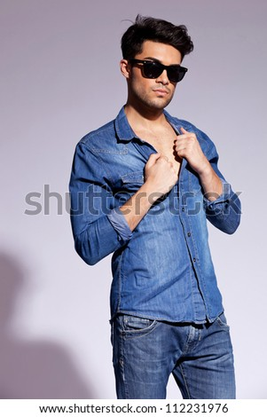 Young attractive fashion man wearing sunglasses and holding his jeans shirt on gray background