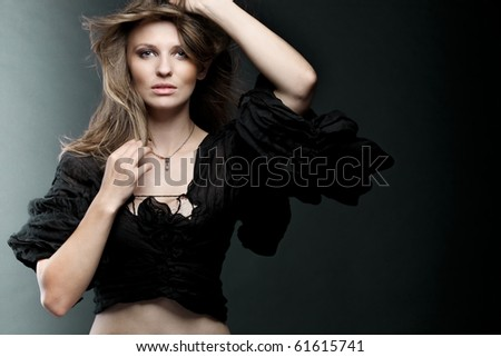 Young attractive fashion model posing on dark background. - stock photo