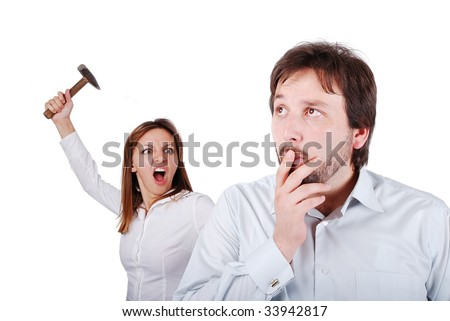 Young attractive female about to hit male from the back with hammer