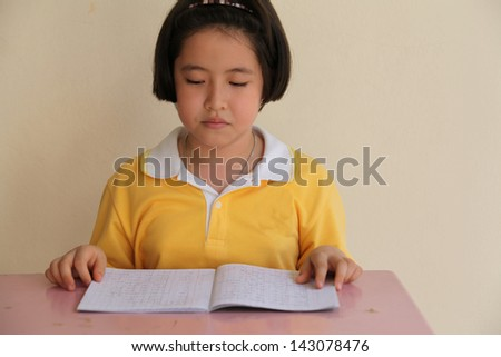Young attractive female Asian student sitting at her desk and reading - stock photo