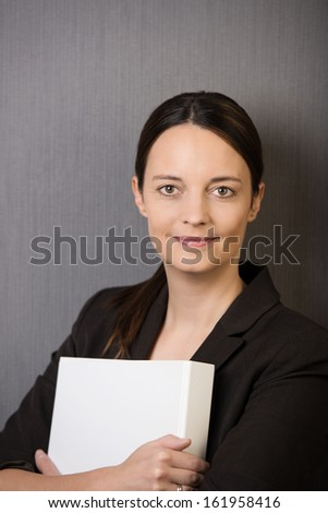 Young attractive female business executive clutching a file to her chest standing looking at the camera with a smile on a grey background - stock photo