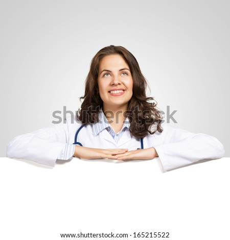 Young attractive female doctor put her hands on the blank banner, place for text