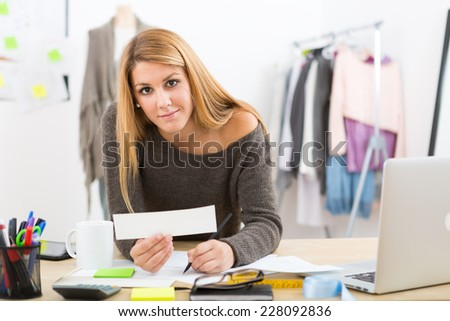 Young attractive female fashion designer leaning on office desk, working with a laptop - stock photo