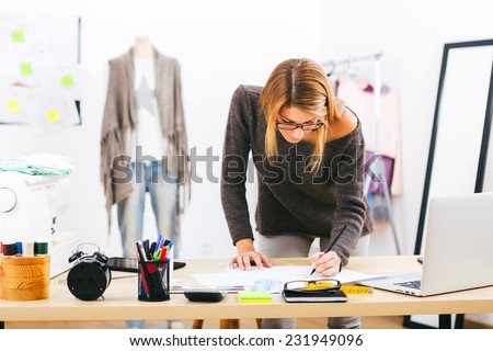 Young attractive female fashion designer leaning on office desk, working with a laptop at home