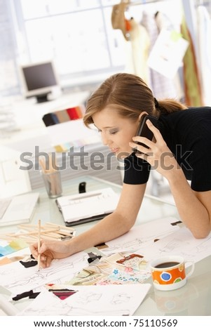 Young attractive female fashion designer working at office desk, drawing while talking on mobile.?