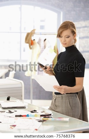 Young attractive female fashion designer working at office desk, using mobile phone, looking at paper. - stock photo