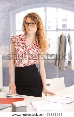 Young attractive female fashion designer working in office at desk.? - stock photo