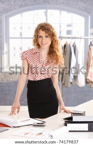 Young attractive female fashion designer working in office at desk, smiling.? - stock photo