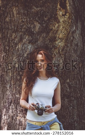 Young attractive female fashion model standing by the brick wall and holding retro camera. - stock photo