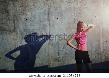 Young attractive female jogger resting after active evening run while standing against concrete wall with copy space area for text message or content, athletic female in bright sportswear taking break - stock photo