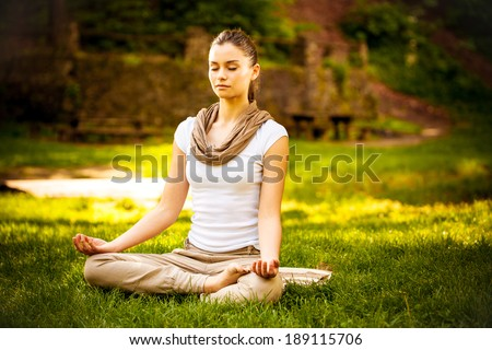 Young attractive female meditate in park. - stock photo