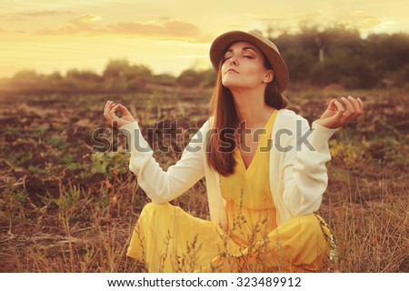 Young attractive female meditate sitting on a deadwood autumn field. - stock photo