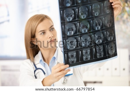 Young attractive female radiologist looking at x-ray image.? - stock photo