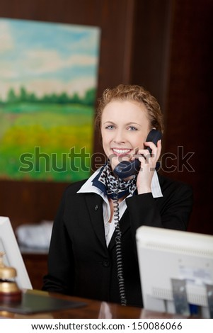 Young attractive female receptionist answering the phone in a hotel - stock photo