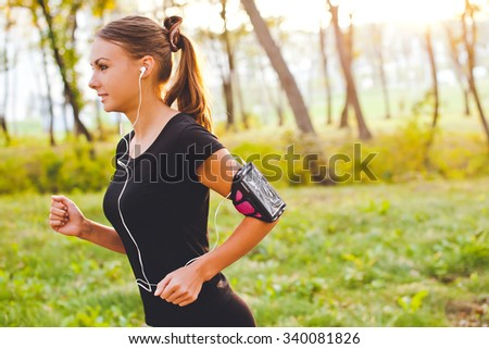 Young attractive female runner with armband running on sunset in park with earphones listening to music during training. Copy space - stock photo