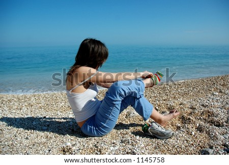 Young attractive female sits on a beach and takes off shoes infront of the Adriatic Sea in the Gargano National Park in Southern Italy