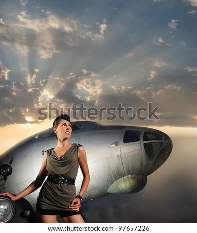Young attractive female soldier with the plane and car - stock photo
