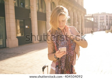 young attractive female student writes a text message on smart-phone. beautiful girl came to Europe for the weekend and booking hotel online. - stock photo