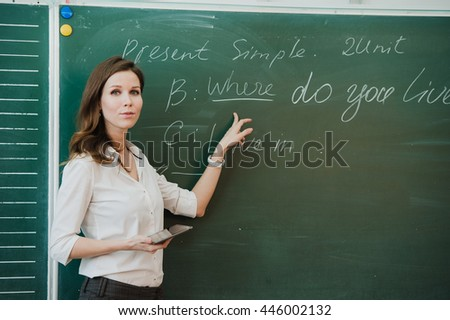 Young attractive female teacher of maths interacting with her young primary school students asking a young girl for an answer - stock photo