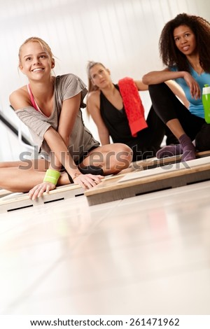 Young attractive females resting after workout at the gym. - stock photo