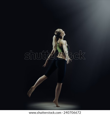 Young attractive fit blond standing on one leg. Isolated on black - stock photo