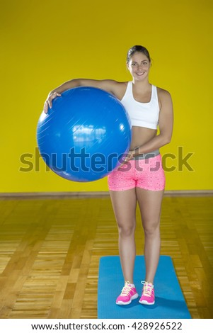 Young attractive fit woman exercises in a fitness room with fitness ball and dumbbells