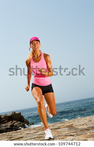 Young attractive fit woman running outdoors at seaside. - stock photo