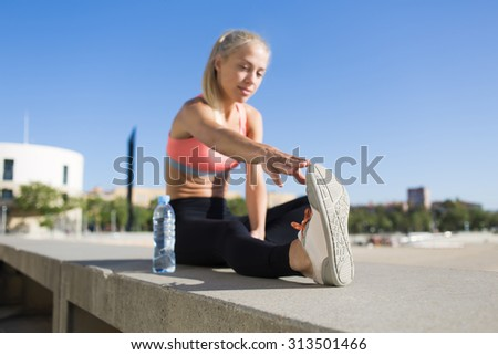 Young attractive fit woman with beautiful figure stretching legs while working out in urban setting at sunny day, caucasian female jogger doing warming up exercise before began her morning run - stock photo