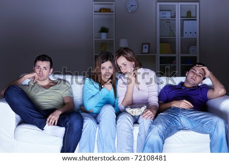Young attractive friends watch movies at home