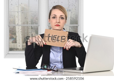 young attractive frustrated businesswoman holding help message overworked at office computer, exhausted, desperate under pressure and stress with rainy sad window view - stock photo