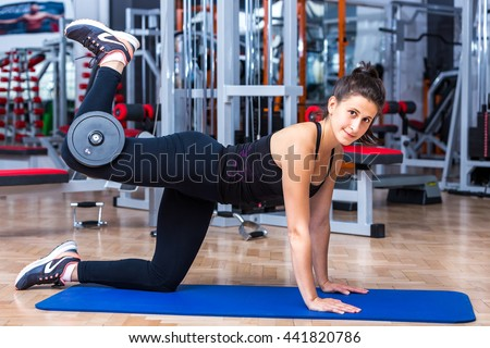 Young, attractive girl at the gym in sportswear while performing the glute kickback exercise with a five kg dumbbell for her gluteus and hamstring muscles. - stock photo