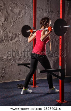 Young attractive girl athlete squats with a barbell. Sport Club. Fitness club. Healthy lifestyle concept. - stock photo