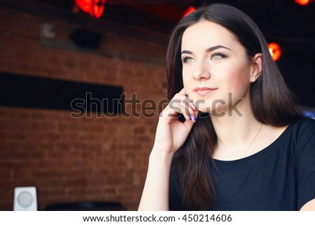 Young attractive girl dressed in black t-shirt posing while sitting alone in modern coffee shop interior. Caucasian female with beautiful smile enjoying her recreation time in cozy cafe bar - stock photo