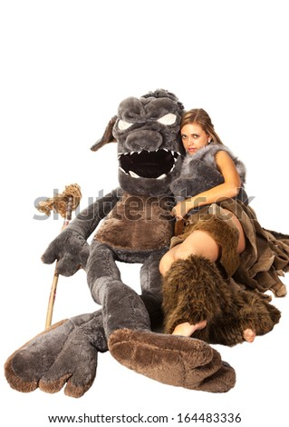 Young attractive girl in costume of savage woman lie with a monster - stock photo