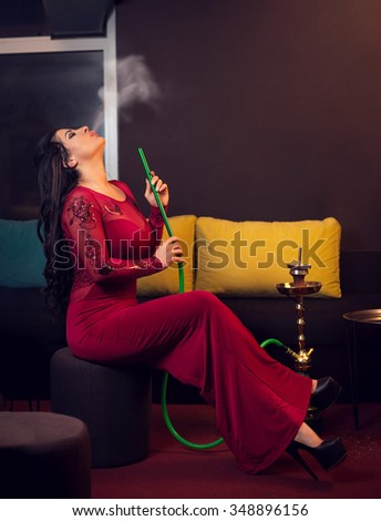 Young attractive girl in elegant dress smoking narghile hookah in bar - stock photo