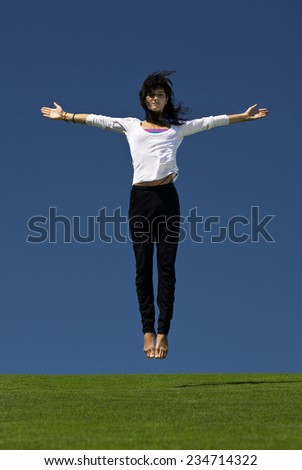 Young attractive girl in flight over a green juicy grass - stock photo