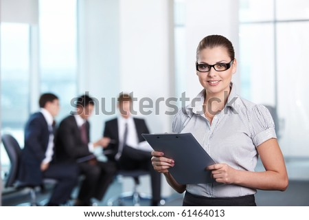 Young attractive girl in the office with clipboard - stock photo