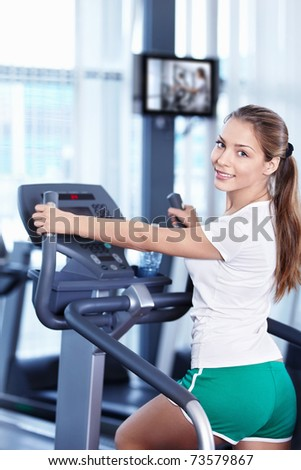 Young attractive girl involved in the simulator - stock photo