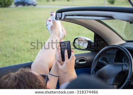 Young attractive girl is sitting with crossed legs in her convertible car and using mobile phone. She is wearing black glasses, white pants and white shirt. In the background is forest.