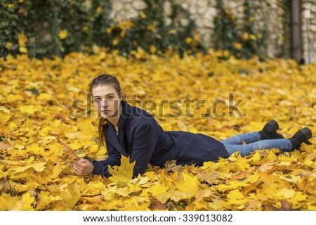 Young attractive girl lying on leaves in autumn Park. - stock photo