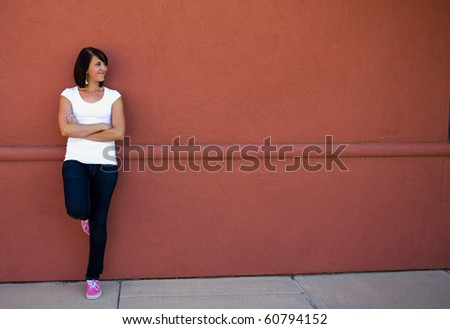 Young attractive girl model posing for a portrait against an outdoor red wall. - stock photo