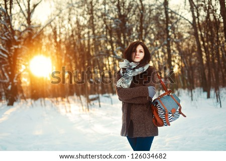 Young attractive girl posing in winter park. Bright sunshine colors - stock photo