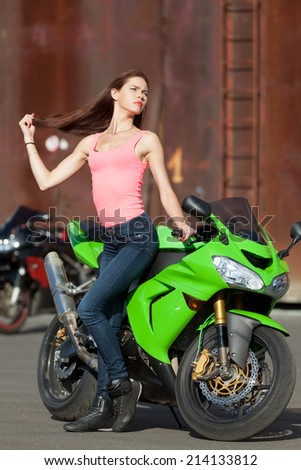 Young attractive girl waiting for her biker to come - stock photo